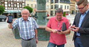 Horst Krippner, Vorsitzender der Antennengemeinschaft, Dietmar Quaas von der Betreiberfirma und Bürgermeister Sven Schrade (von li.) loggen sich ins WLAN auf dem Schmöllner Markt ein. (Foto: J. Hiller, Stadtverwaltung Schmölln)