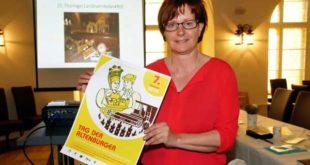"""Susanne Stützner (Schloss- und Kulturbetrieb) mit einem Plakat, das für den """"Tag der Altenburger"""" wirbt und auf dem Treffen der Arbeitsgruppe im Ratskeller vorgestellt wurde. (Foto: Ronny Seifarth)"""