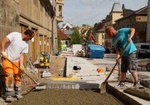 Tobias Gurski (l.) und René Wähler beim Verlegen der Gehwegplatten. (Foto: Ronny Seifarth )